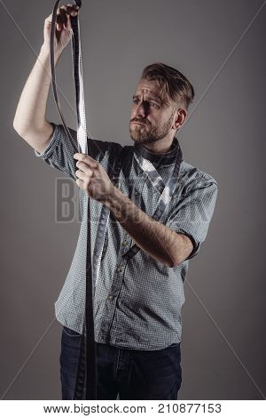 Trendy Man Looks At The Quality Of The Captured Film On Gray Background