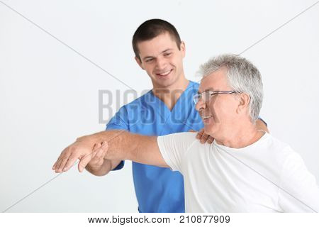 Physiotherapist working with senior patient on white background