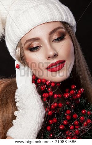 Beautiful girl in a white cap and gauntlets holding a Christmas tree balls red. Professional make-up her lips scarlet photographed in the studio on an isolated black background. Christmas theme.