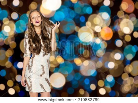 holidays, hairstyle and people concept - happy young woman or teen girl in fancy dress with sequins touching long wavy hair over festive lights background