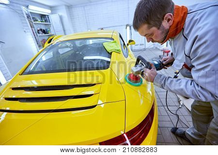 Polishing the yellow machine for customer service.