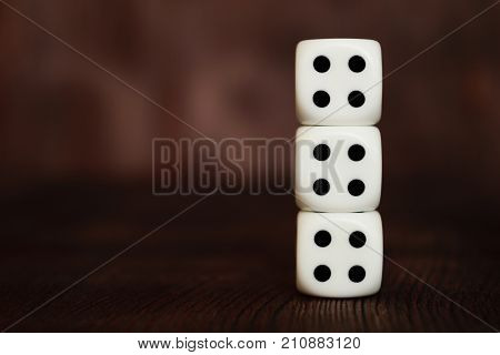 Three white plastic dices column on dark brown wooden board background. Six sides cube with black dots. Unlucky number four - 4. Tetraphobia concept.