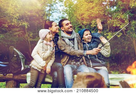 travel, tourism, hike and technology concept - happy family sitting on bench and taking picture with smartphone on selfie stick at campfire in woods