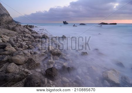 Rocky coast immediately after sunset stones in milky waves undulating water. long expositure