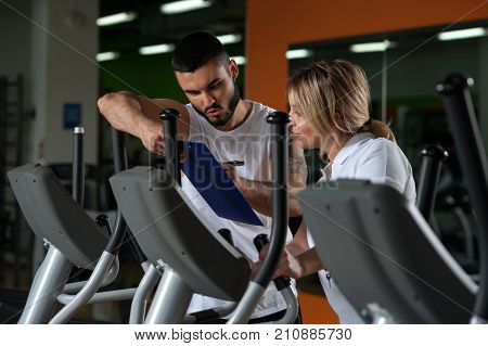 Portrait of middle aged brunette woman working out with personal coach in modern fitness center. Male trainer and female client discussing nutrition or training plan. Healthy lifestyle concept.