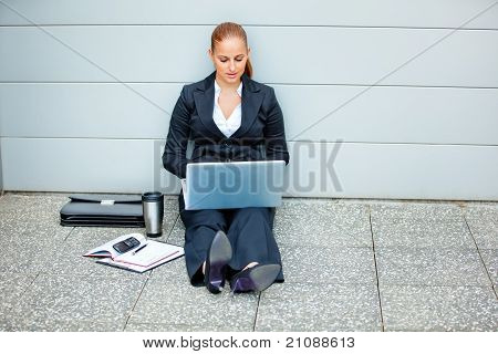 Pensive modern business woman sitting on floor at office building and using laptop