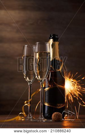 Picture of two wine glasses with sparkling champagne, bottle,