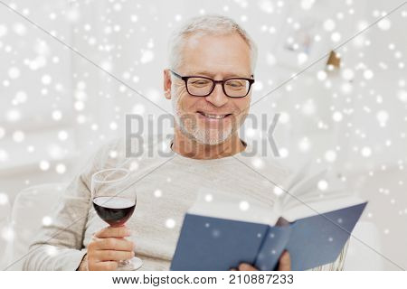 age, leisure and people concept - happy smiling senior man with wine glass reading book at home over snow