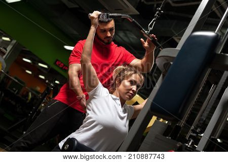 Middle aged blonde woman working out with personal fitness coach. Young male trainer assisting female client in gym. Healthy lifestyle, fitness and sports concept.