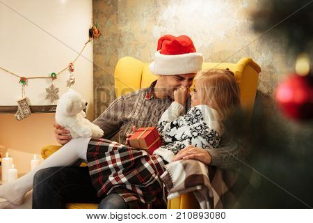 Little blonde kid tweaks her fathers nose while sitting on his knees in chair n living room with Christmas decor