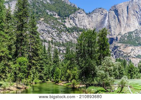 The Merced river on a late July afternoon, with the upper yosemite falls in the background. Yosemite National Park, California, USA.