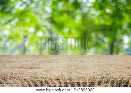 Empty table and sack tablecloth over blur tree with bokeh background for product display montage
