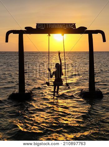 Silhouette of Beautifull Gate with girls swing above ocean sunset. Gili Trawangan island Lombok Indonesia