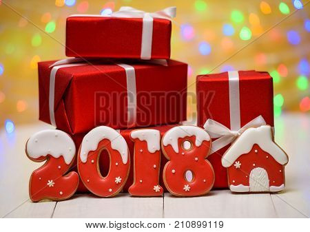New year 2018 made with gingerbread cookies with bokeh and lens flare pattern on golden background copy space. New Year 2018 or Christmas postcard with gingerbread cookies and red gift boxes