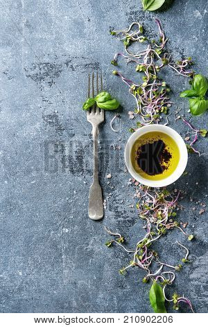 Young radish sprouts with pink himalayan salt and basil leaves with bowl of olive oil and balsamic vinegar over blue texture background. Top view with copy space. Healthy diet concept, food background