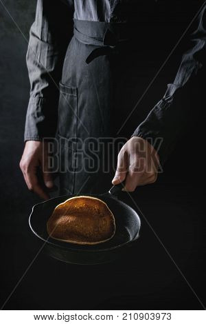 Man chef in black apron cooking pancakes in cast-iron pan. Tossing a pancake in the air. Dark rustic style.