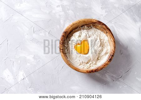 Olive wood bowl with wheat flour and whole egg yolk as heart shape over gray texture background. Top view with copy space. Baking concept