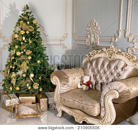A Christmas tree in a cozy house in classic style. The symbol of the new 2018 is Yellow Dog. All ornaments in New Year's interior should be yellow or gold.