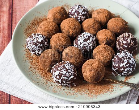 Homemade chocolate truffles with cocoa and coconut on the plate