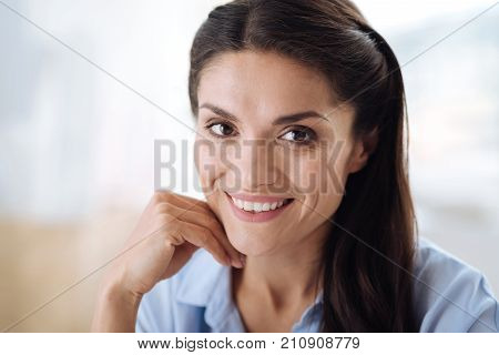 Beautiful face. Portrait of a nice happy attractive woman smiling and looking at you while being in a good mood