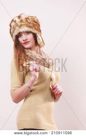 Winter fashion. Young woman wearing fashionable wintertime clothes fur cap woolen sweater studio shot on gray