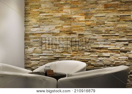 Corner of waiting area with four white soft armchairs and brown round coffee table near stone wall and white column.