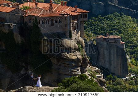 Meteora Greece - 9 October 2017: Wedding couple holding hands on a rock at Meteora with Varlaam Monastery in the background. Shot in landscape format