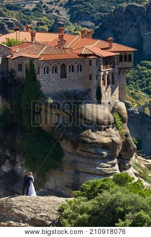 Meteora Greece - 9 October 2017: Groom embracing bride on a rock at Meteora with Varlaam Monastery in the background. Shot in portrait format