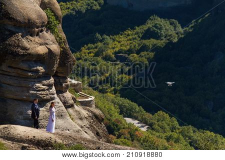 Meteora Greece - 9 October 2017: Wedding couple gazing and standing on a rock at Meteora with Varlaam Monastery in the background as a drone shoots