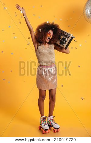 Full length portrait of beautiful overjoyed afro american disco woman with raised hand, standing on roller skates, holding boombox, isolated on yellow background