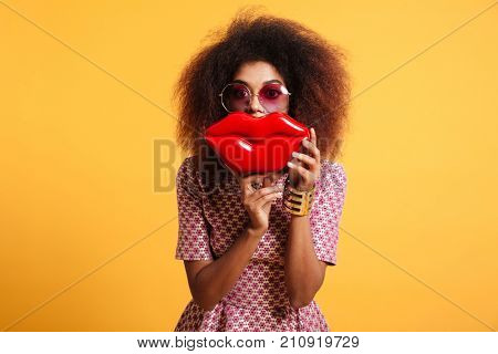 Close-up portrait of playful african woman in sunglasses holding big red lips in front of her face, looking at camera, isolated on yellow background