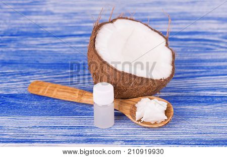Half of coconut, pieces of coconut, coconut flakes and coconut glaas jar on wooden background. Healthy food concept