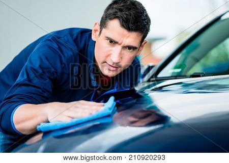 Young man using an absorbent soft towel for drying and polishing the surface of a clean blue car