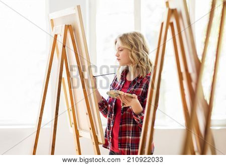 art school, creativity and people concept - student girl or artist with easel, palette and paint brush painting at studio