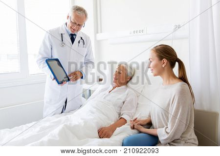 medicine, healthcare and people concept - senior woman patient with daughter and doctor with tablet pc computer at hospital ward