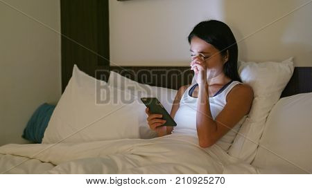 Woman feeling eye pain when using cellphone at night