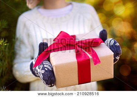 close-up of nicely wrapped christmas gift held by little kid winter holiday or christmas concept