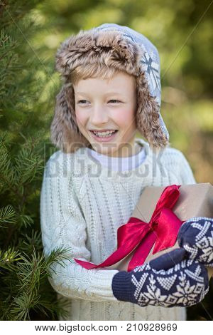 beautiful smiling boy in trapper hat and mittens holding christmas gift standing by the tree winter holiday concept poster