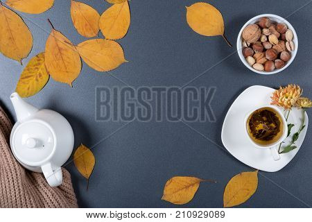 Romantic autumn working desk. Yellow and orange leaves white cup of herbal tea teapot warm scarf and nuts. Healthy snack. Top view. Flat lay.
