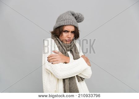 Portrait of a young frozen girl in scarf and hat holding arms folded and looking at camera isolated over gray background