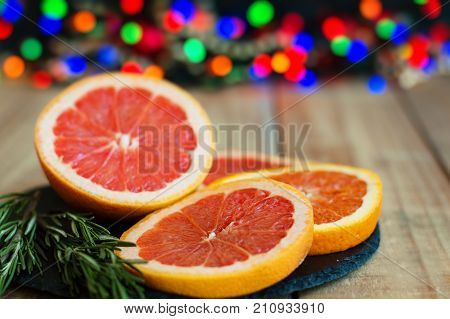 Sliced orange and grapefruit served with fresh rosemary on black slate board blurred lights as background. Christmas mood
