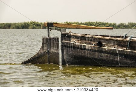 sailing old wooden boat on a lake, submerged part of the steering boat rudder blade, rudder primary control surface to steer, cane and rudder, shovel of the rudder blade
