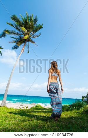 Woman stands on the coast of a sea and enjoys the view