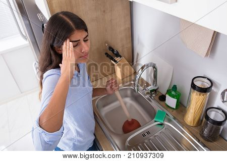 High Angle View Of A Young Unhappy Woman Using Plunger In Clogged Sink