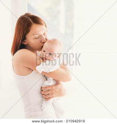 Portrait of Mother and Baby. Beautiful woman holding a baby child in her arms. Image of happy maternity and family.