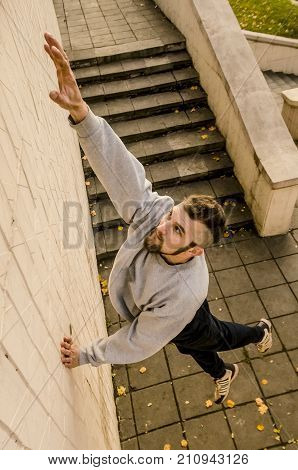A Young Guy Overcomes Obstacles, Climbing On Concrete Walls. The Athlete Practices Parkour, Training