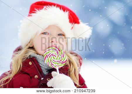 Adorable Little Girl Wearing Santa Hat Having Huge Striped Christmas Lollipop On Beautiful Winter Da