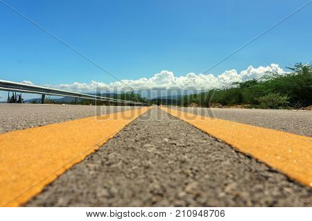 yellow dividing lines on asphalt road or highway close-up