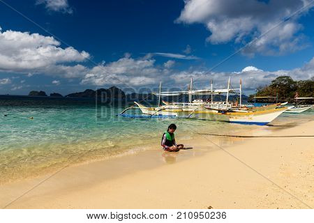 A Girl Playing With Sand On The Seashore In A Beach Of El Nido.