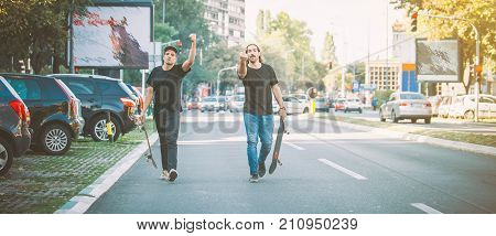 Two pro skateboard rider walking down the street holding their skateboards in hand. Urban skate scene